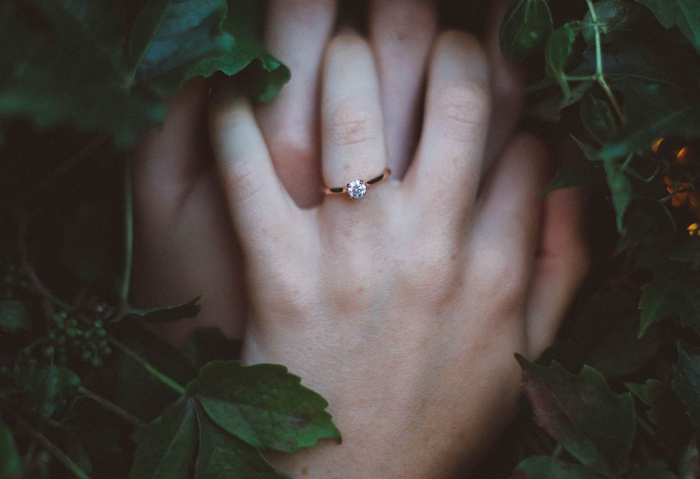 Gold-Colored Ring on Hands Surrounded By Green Foliage